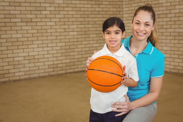 Student holding basketball with teacher