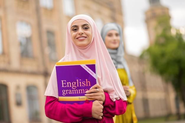 학생 보유 책입니다. 친구 근처에 서있는 동안 분홍색 hijab 지주 책을 입고 아름다운 이슬람 학생