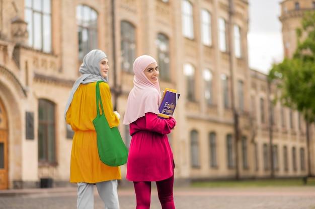학생 보유 책입니다. 친구와 함께 수업에 책을 들고 웃는 이슬람 학생