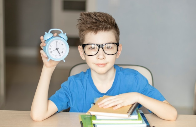 The student holds an alarm clock in his hands. time to learning.