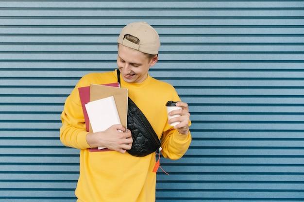 Студент в кепке и желтом свитшоте стоит