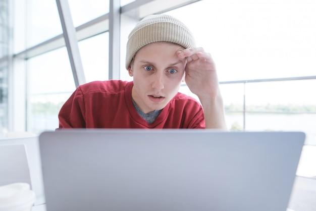 Студентка в стильном повседневном платье сидит в кафе и смотрит на экран ноутбука
