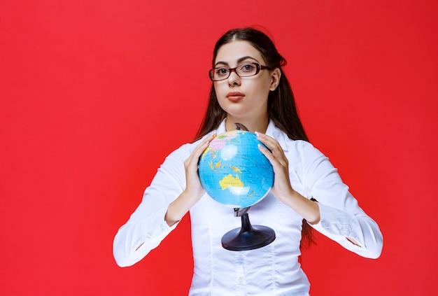 世界の地球儀を持って紹介する眼鏡の学生。