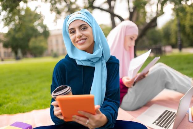 히잡의 학생. 태블릿과 커피를 들고 밝은 파란색 hijab를 입고 아름다운 이슬람 학생