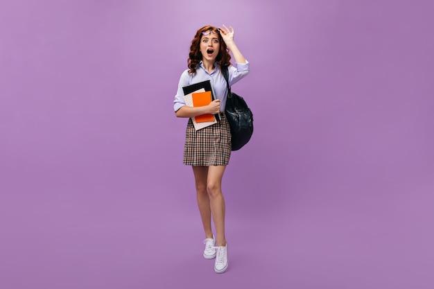 格子縞のスカートの学生はノートを保持します