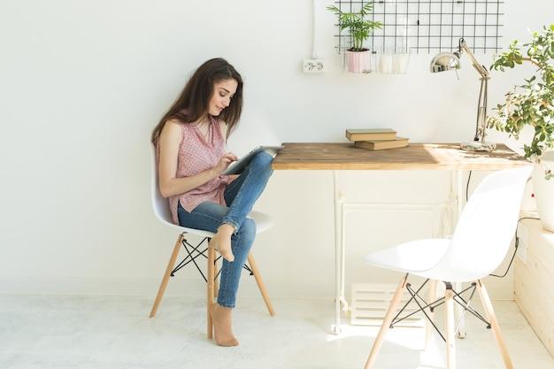Студент сидит на стуле и использует цифровой планшет или просматривает интернет