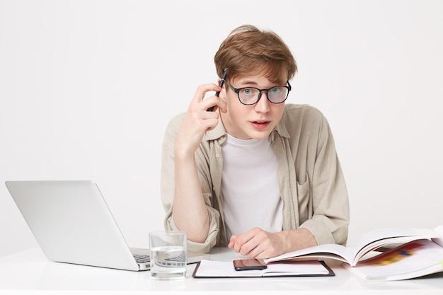 Lo studente è seduto al tavolo, libri di testo e quaderni sono disposti di fronte a lui