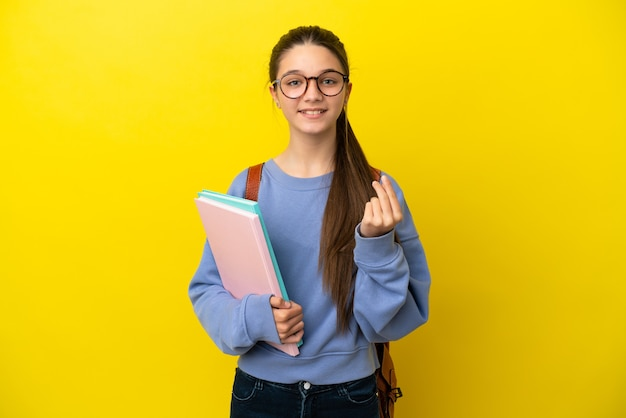 Student kid woman over isolated yellow background making money gesture