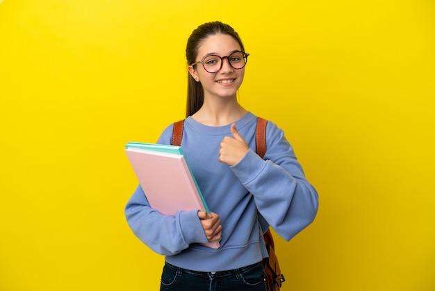고립 된 노란색 배경 위에 엄지손가락 제스처를 주는 학생 아이 여자