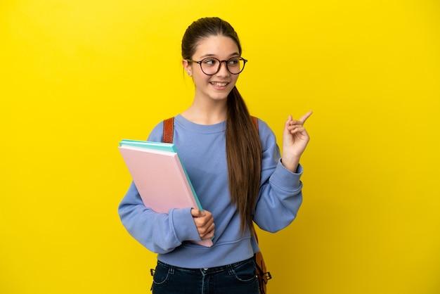 Студент ребенок женщина на изолированном желтом фоне, намереваясь понять решение, подняв палец вверх