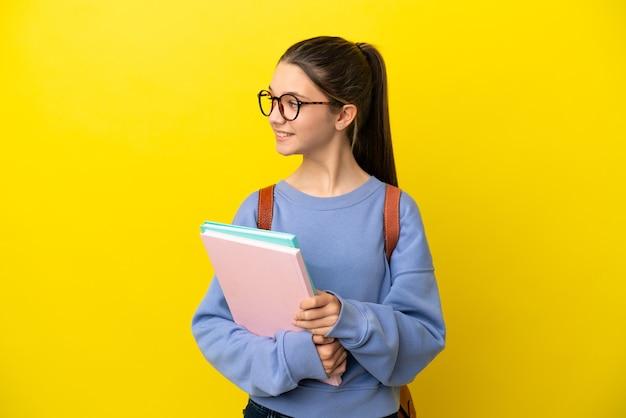 고립 된 노란색 배경 찾고 측면을 통해 학생 아이 여자