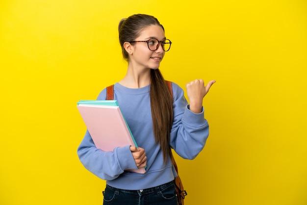 제품을 제시하기 위해 측면을 가리키는 고립된 노란색 배경 위에 학생 아이 여자
