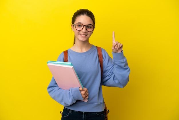Студент ребенок женщина на изолированном желтом фоне, указывая вверх отличная идея