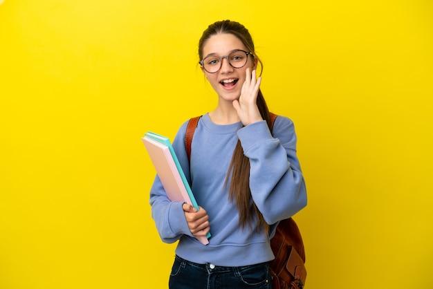 Студент ребенок женщина на изолированном желтом фоне кричит с широко открытым ртом