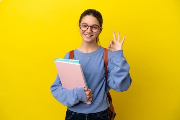 Студент ребенок женщина на изолированном желтом фоне показывает знак ок пальцами
