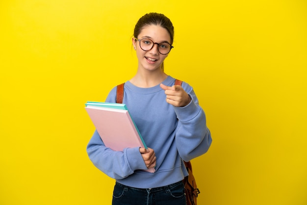 Студент ребенок женщина на изолированном желтом фоне удивлен и указывая вперед