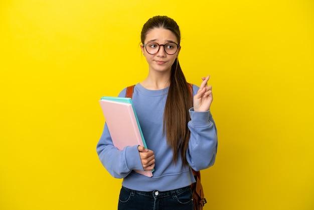 Женщина-студент-ребенок на изолированном желтом фоне со скрещенными пальцами и желанием всего наилучшего