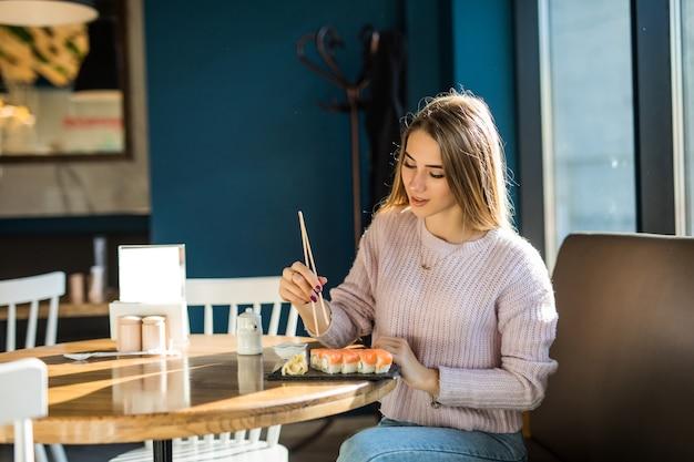 Студентка в белом свитере ест суши на обед в маленьком кафе