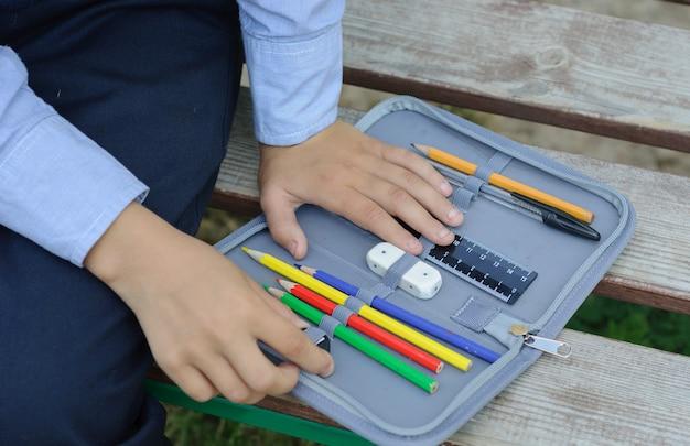Студент раскладывает предметы в школьном пенале, сидя на скамейке