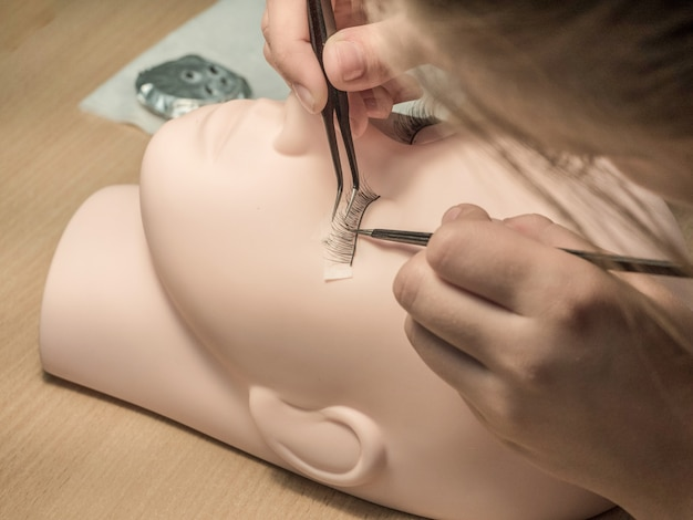 Student learning eyelash extensions on a mannequin.