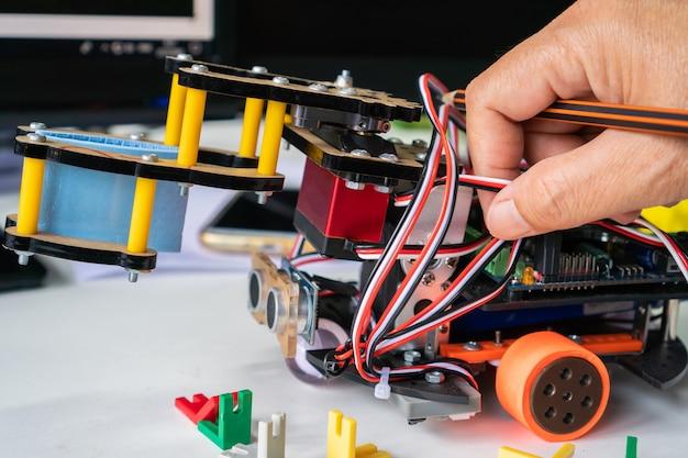 学校の実験室でロボット工学の電子機器によってプログラムされるための電子ボードでの学生の学習。 diyイノベーションのための数学、工学、科学、技術の概念