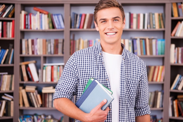 Student in library. handsome young man holding books and smiling while standing in library