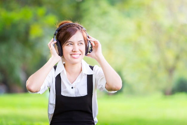 Student listen music after read book in park of university