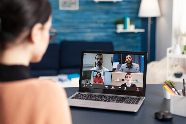 ラップトップコンピューターを使用したオンラインビデオ通話学校の会議中に同僚を聞いている学生。居間に座ってコロナウイルス検疫中に遠隔教育を受けている若い女性