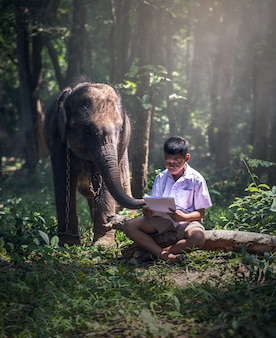Student little asian boy with him elephant, countryside in thailand
