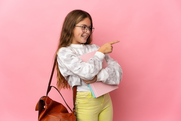 Student little girl over isolated pink background pointing finger to the side and presenting a product