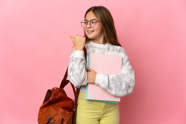 Student little girl over isolated pink background pointing to the side to present a product