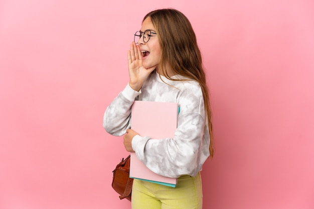 Student little girl over isolated pink background shouting with mouth wide open to the side
