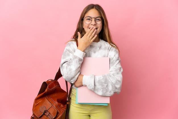 Студент маленькая девочка на изолированном розовом фоне счастлива и улыбается, прикрывая рот рукой