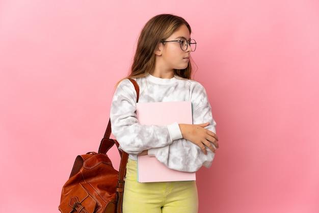 横に見て孤立したピンクの背景の上の学生の少女