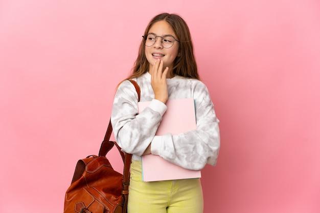 Студент маленькая девочка на изолированном розовом фоне, глядя вверх, улыбаясь