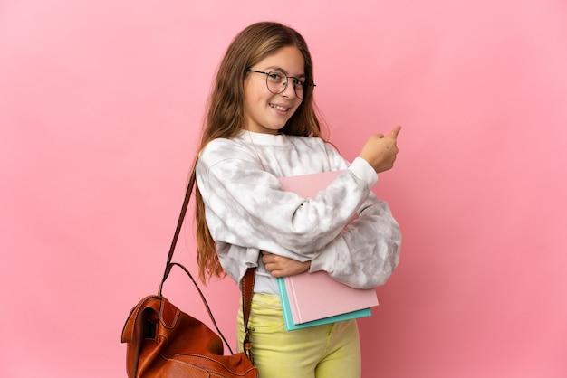 後ろ向きの孤立したピンクの背景の上の学生の少女