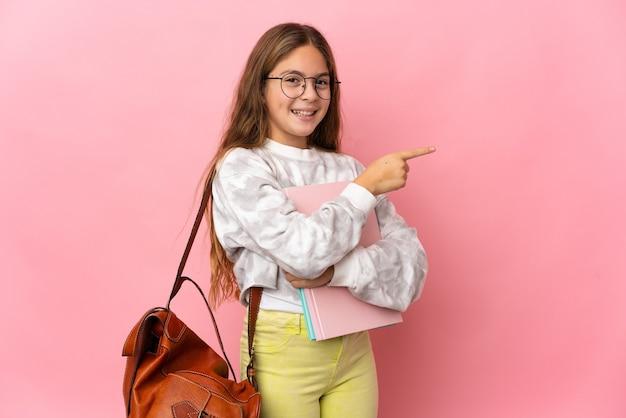 Студент маленькая девочка на изолированном розовом фоне, указывая пальцем в сторону