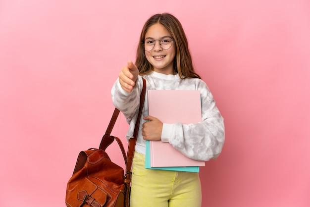 좋은 거래를 닫기 위해 악수 고립 된 분홍색 배경 위에 학생 어린 소녀