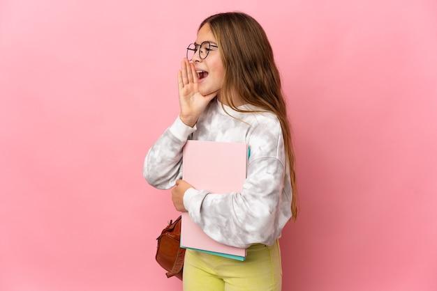 Маленькая девочка студента на изолированном розовом фоне кричит с широко открытым ртом в сторону