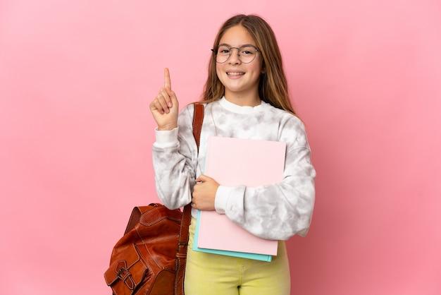 孤立したピンクの背景の上の学生の少女は、最高の兆候を示して指を持ち上げます