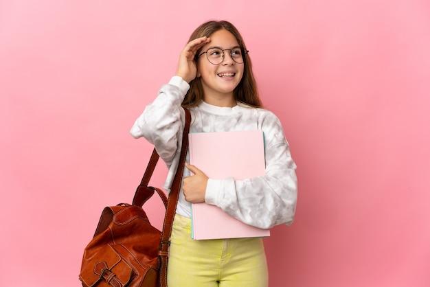 Студент маленькая девочка на изолированном розовом фоне много улыбается