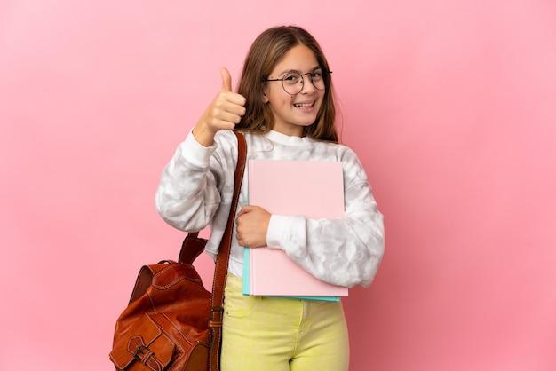 Маленькая девочка студента на изолированном розовом фоне с большими пальцами руки вверх, потому что случилось что-то хорошее