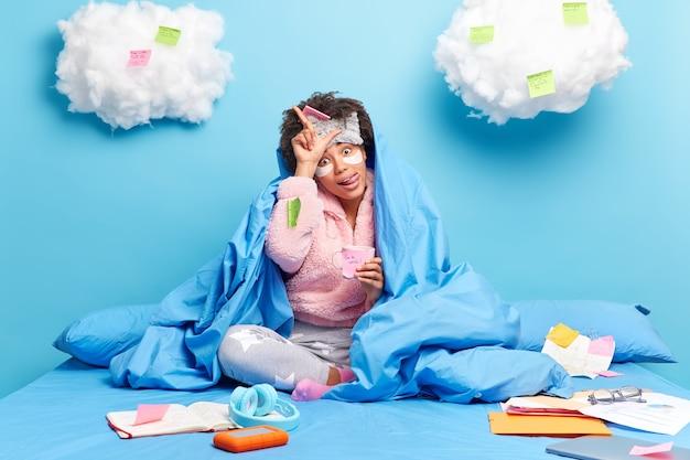 Lo studente fa il gesto del perdente sporge la lingua avvolta in una coperta studia a casa posa sul letto ha una pausa caffè