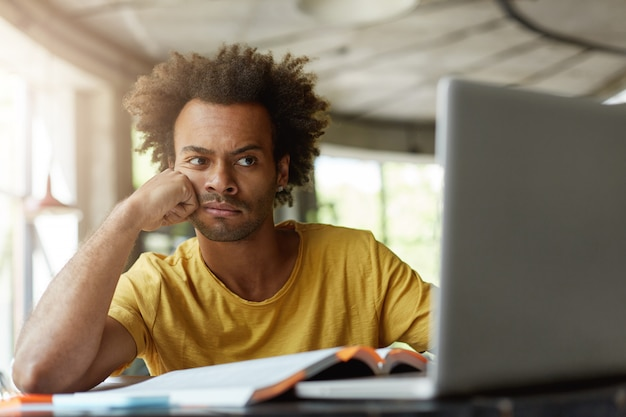 Студент-мужчина с густыми волосами и темной кожей со скучающим выражением лица устал от учебы, сидя в кафе в окружении книг и записной книжки, выполняя свой исследовательский проект с использованием бесплатного интернета