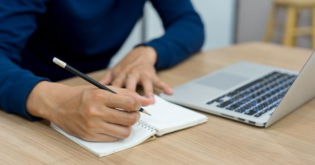 ノートパソコンに書くために鉛筆を使用して学生の男の手