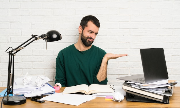 Student man holding copyspace with doubts