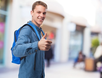 Student man with back-pack doing okay sign