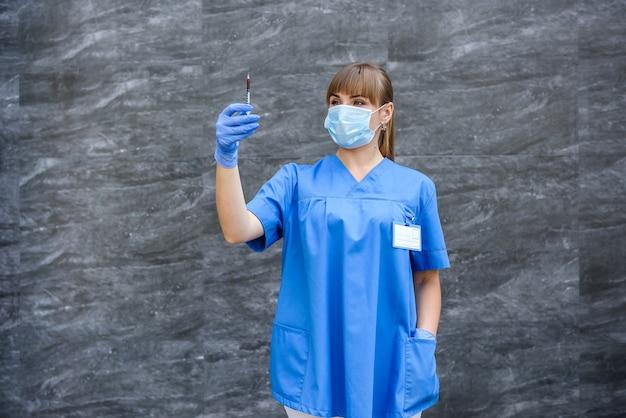 血でインスリン注射器を保持している学生看護師。