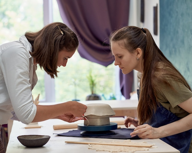 Студент сосредоточенно наблюдает за работой мастера лепки из глины.