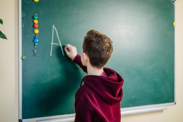 Студент высшей школы стоит в темной толстовке рядом с зеленой доской в классе. подросток пишет алфавит на доске. концепция школьного образования.